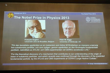 Images of Francois Englert of Belgium and Britain's Peter Higgs, laureates of the 2013 Nobel Prize in Physics, are displayed on a screen during a news conference in Stockholm
