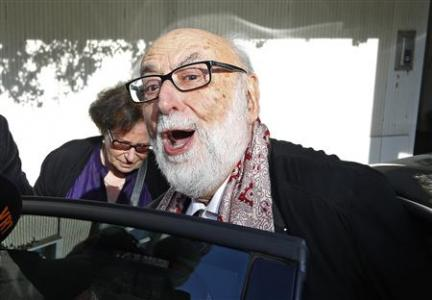 Belgian physicist Francois Englert leaves his house with his wife Mira in Brussels, after he and Britain's Peter Higgs won the Nobel prize for physics